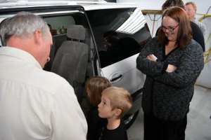 Randi Greene, right, looks on as her 6-year-old twins, Isaac and Lola, make their way into the 2005 Kia Sedona minivan she and her family received Monday, Dec. 15, as part the PAT's CARSTAR Recycled Rides program.
