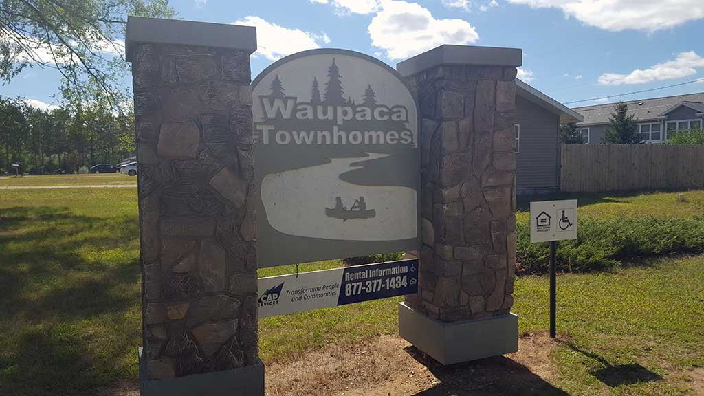 Waupaca Townhomes exterior with sign